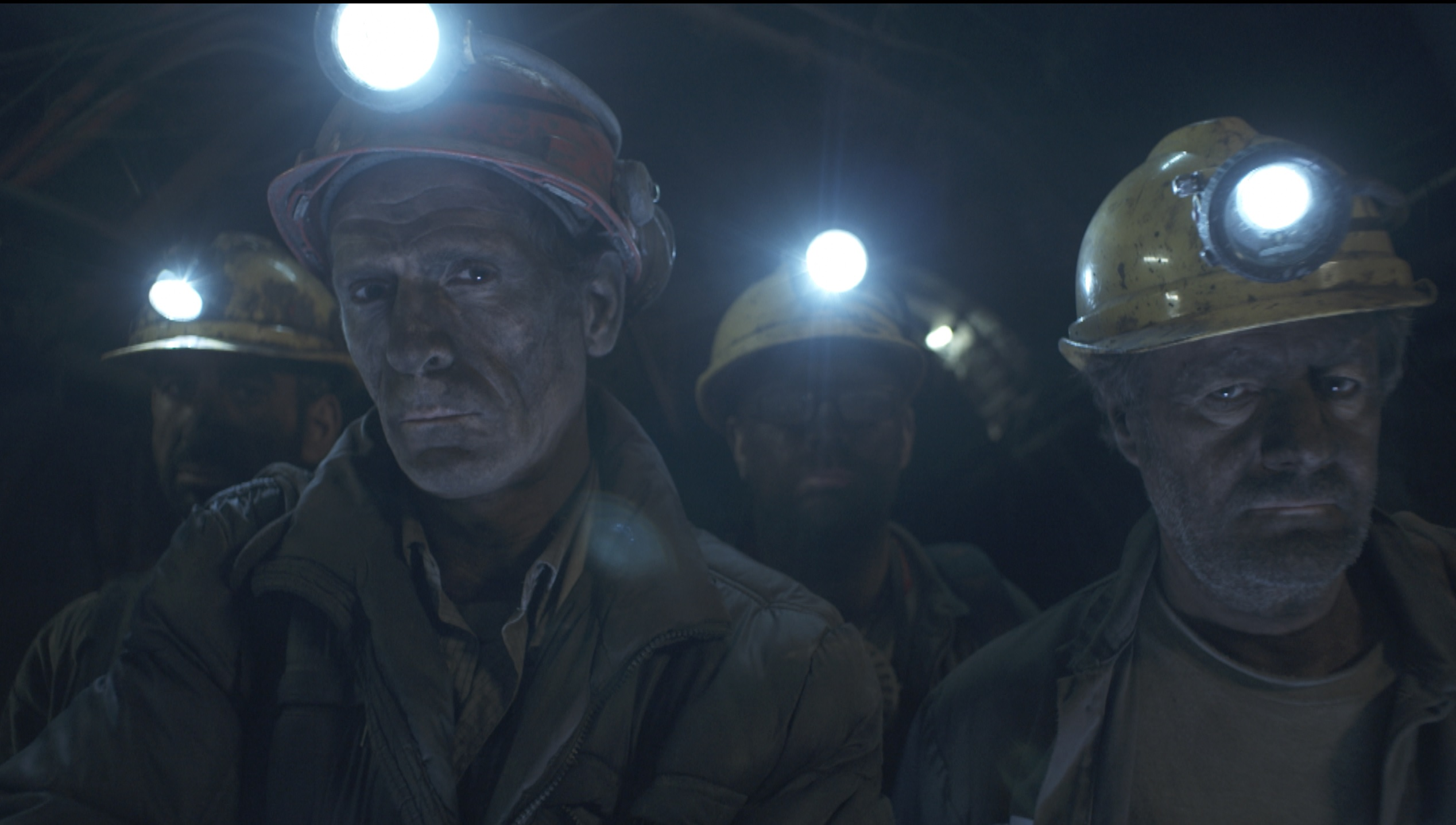 A group of miners look at us in the documentary From The Depths