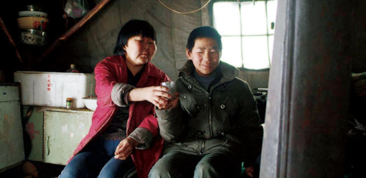 A Chinese mother and her son in their humble house in the film Yuguo And His Mother