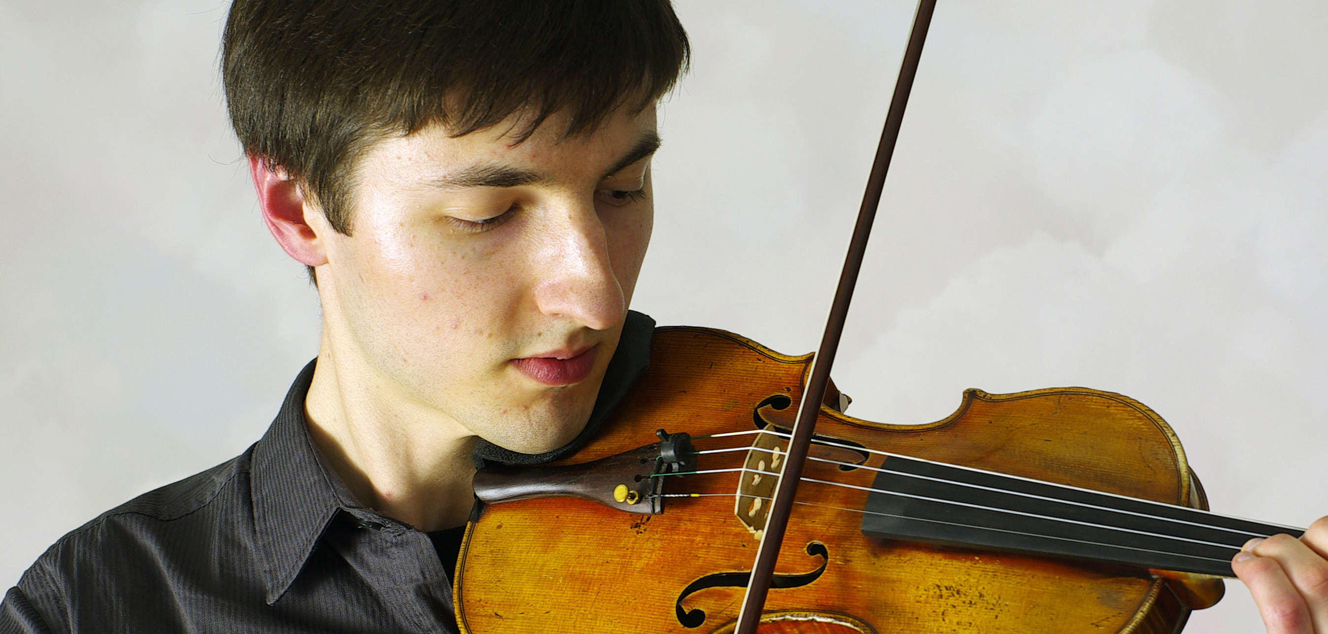 """A young man plays violin in the documentary """"Carry The Tune"""""""