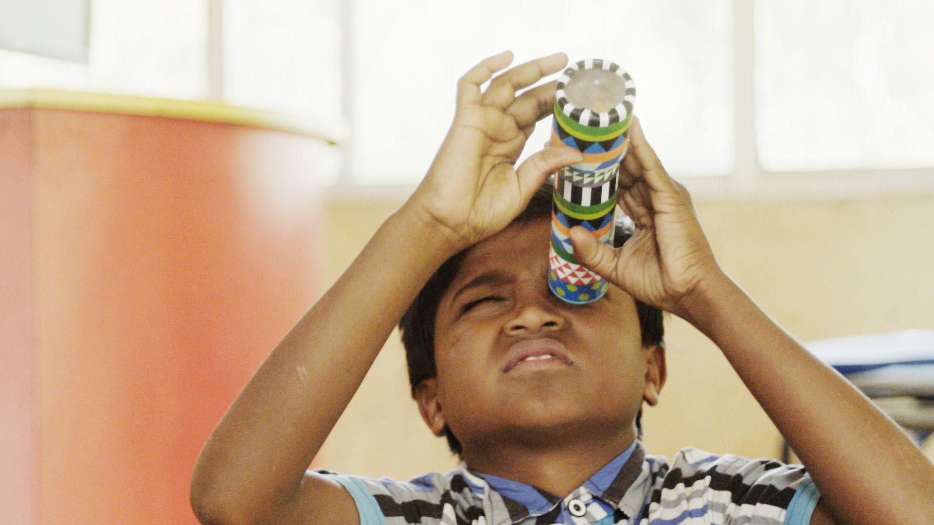 An indian boy looks through a kaleidoscope