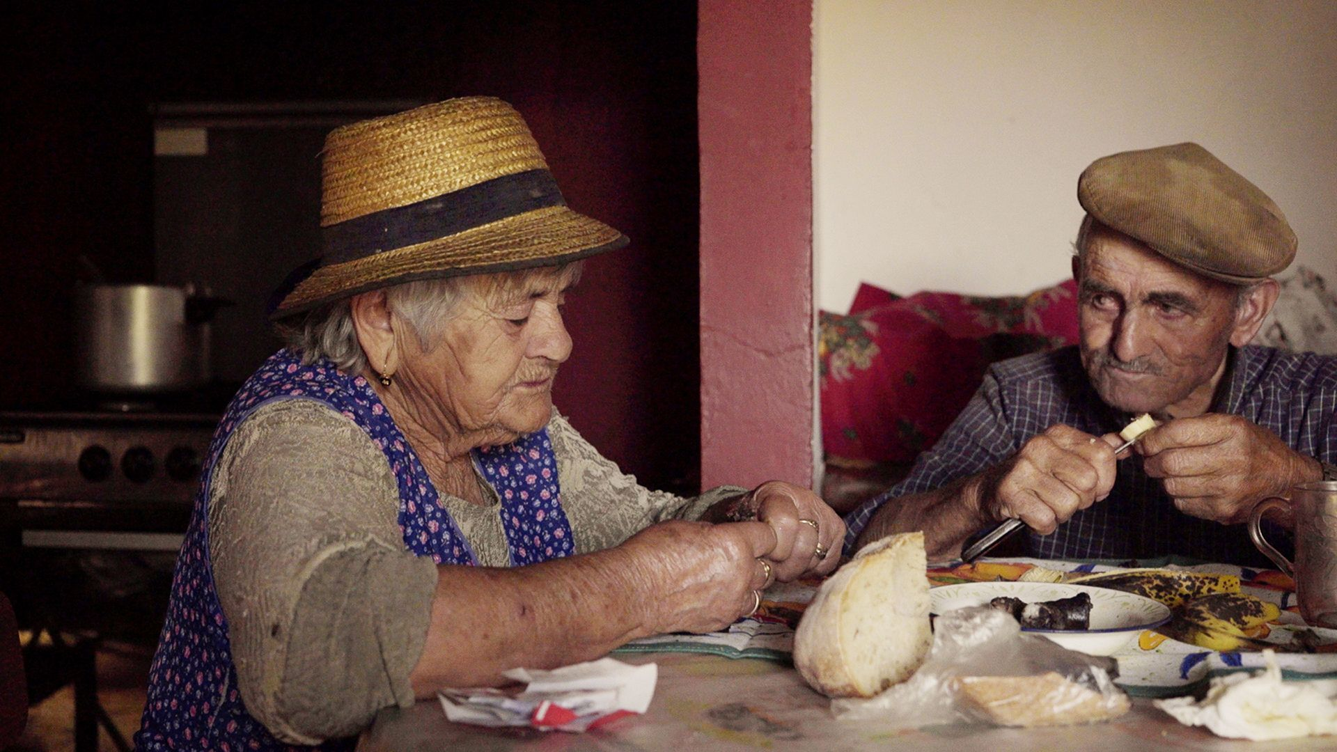 Inacio and an old woman, her neighbor, in a house in his portuguese village