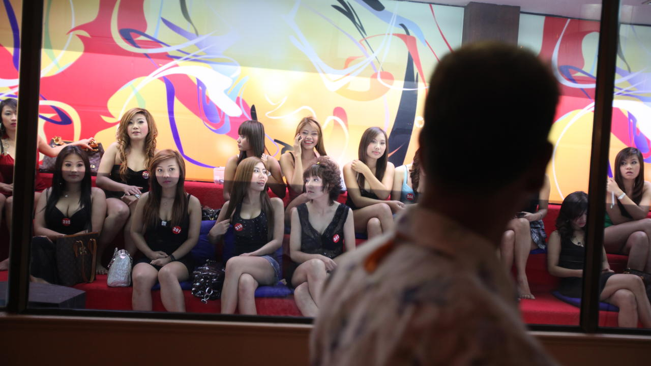 A group of prostitutes in Thayland sit in the documentary Whore's Glory